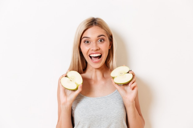 Portrait of a happy excited in underwear holding sliced apple
