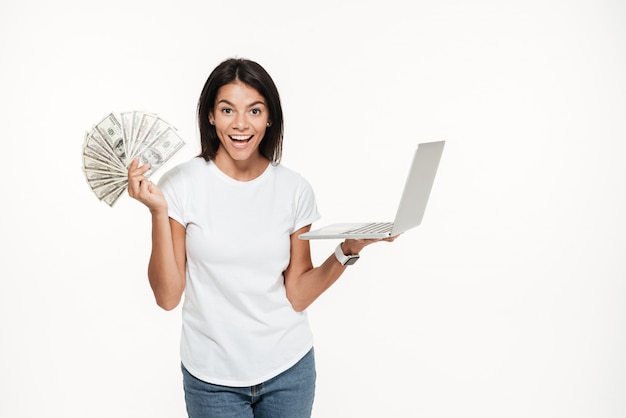 Portrait of a happy excited woman holding laptop computer