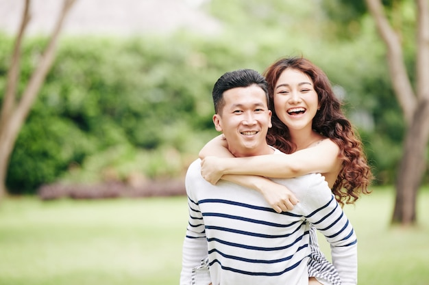 Portrait of happy excited young vietnamese couple hugging and looking at camera