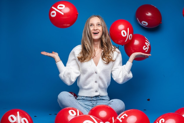 Portrait of happy fair-haired girl in white cardigan and jeans holding arms half bent and looking at flying red balloons with sale word and percent sign