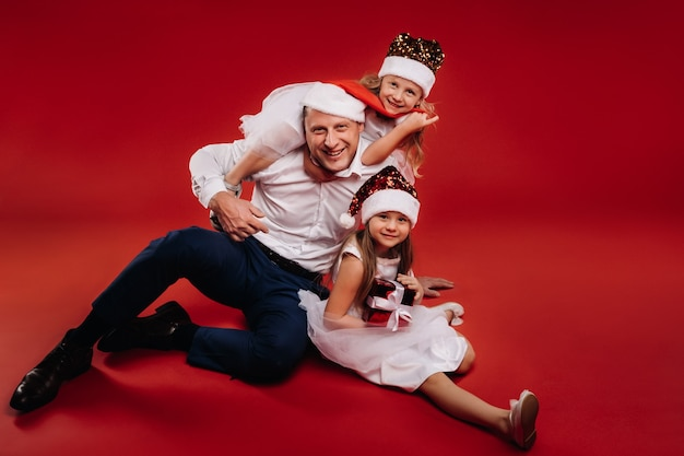 Portrait of a happy family in a christmas hat on a red background. dad and daughters at christmas.
