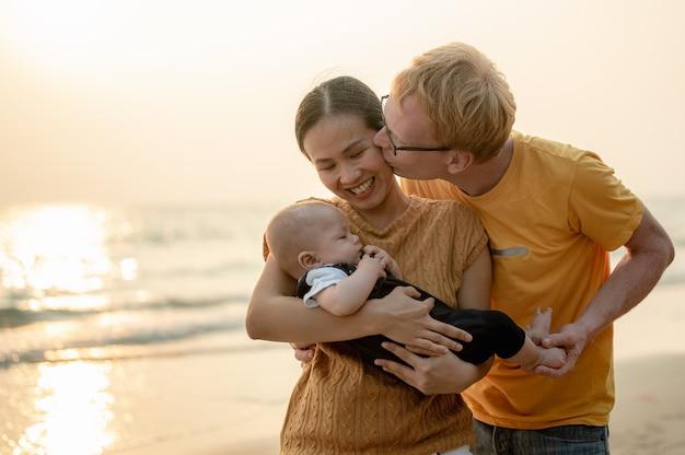 肖像画幸せな家族の休日夫は彼の妻の頬にキスをしていた父赤ちゃん息子の散歩