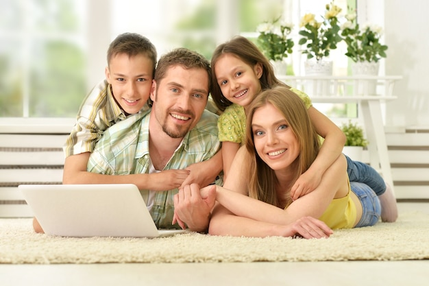 Portrait of happy family at home with laptop