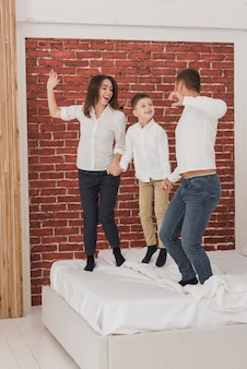 Portrait of happy family jumping in bed