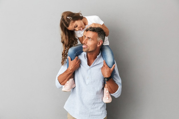 Portrait of happy family little girl and adult man having fun while daughter sitting on the neck of her father, isolated over gray