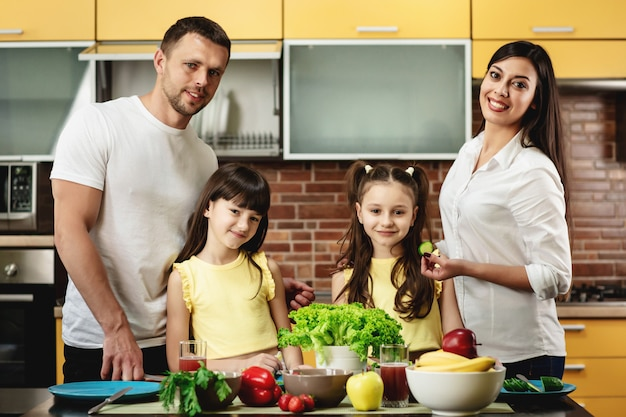 Portrait of a happy family, mom dad and two daughters, cooking salads in kitchen at home. healthy eating concept