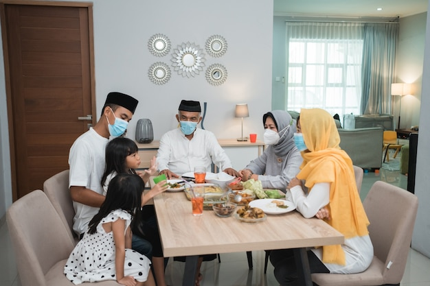Portrait of happy family muslim wear mask during eid mubarak celebration at home