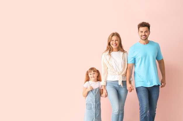 Portrait of happy family near color wall
