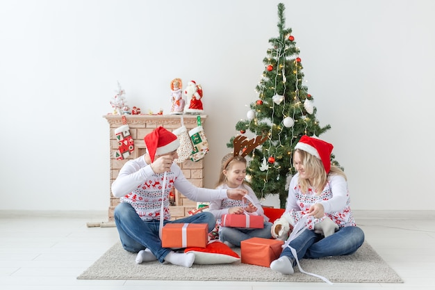 Portrait of a happy family opening gifts at christmas time