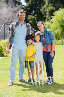 Portrait of happy family playing cricket together in backyard
