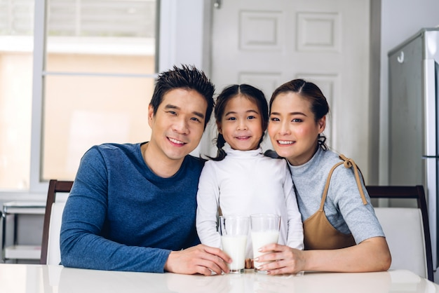 Portrait of happy family posing and drinking milk