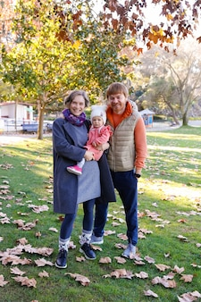 Portrait of happy family standing in autumn park together and smiling. cheerful mother holding cute baby