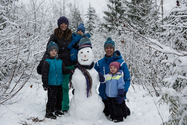 Portrait of happy family standing by snowman