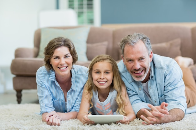 Portrait of happy family using digital tablet while lying on floor in living room