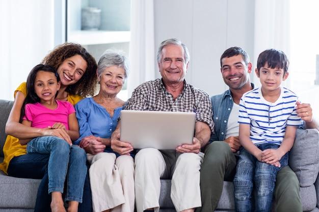 Portrait of happy family using laptop on sofa