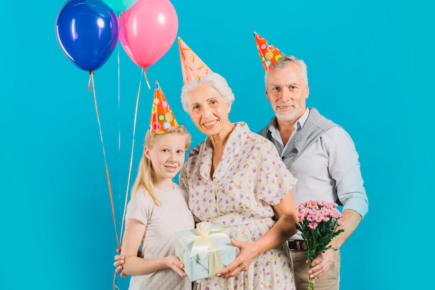 Portrait of happy family with birthday gift; balloons and flowers on blue backdrop