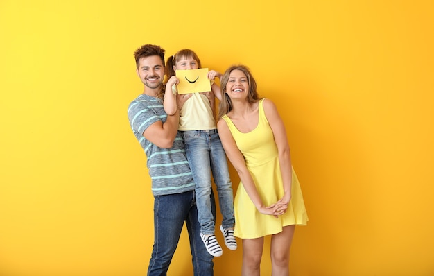 Portrait of happy family with drawn smile on sheet of paper against color