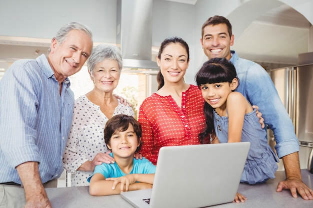 Portrait of happy family with laptop at home