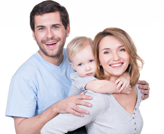 Ritratto della famiglia felice con il bambino piccolo che guarda l'obbiettivo - isolato