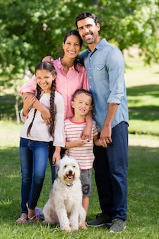 Portrait of happy family with their pet dog standing in park