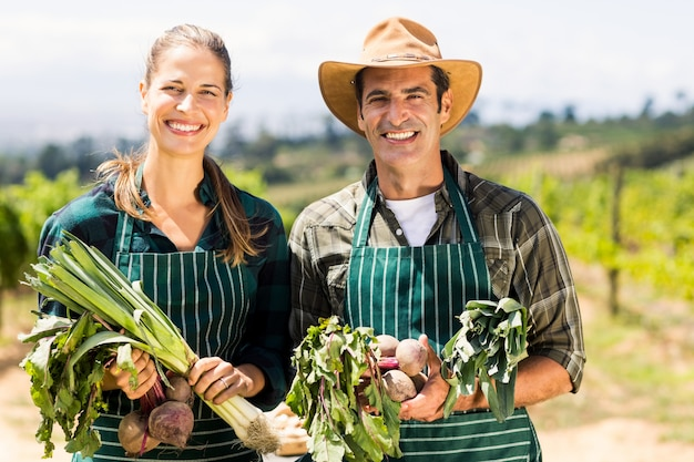 Portrait of happy farmer couple holding leafy vegetables