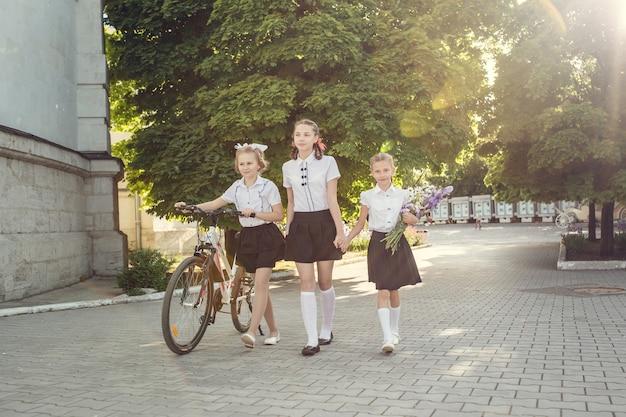Portrait of happy fashion little kids having fun with bike in city.