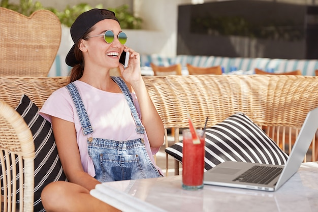 Portrait of happy fashionable young woman in sunglasses and black cap, sits against cafe interior, enjoys mobile conversation, works on laptop computer, shares positive news with best friend