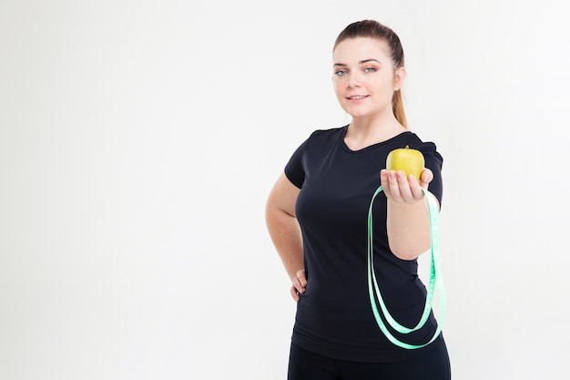 Portrait of a happy fat woman holding apple isolated on a white wall