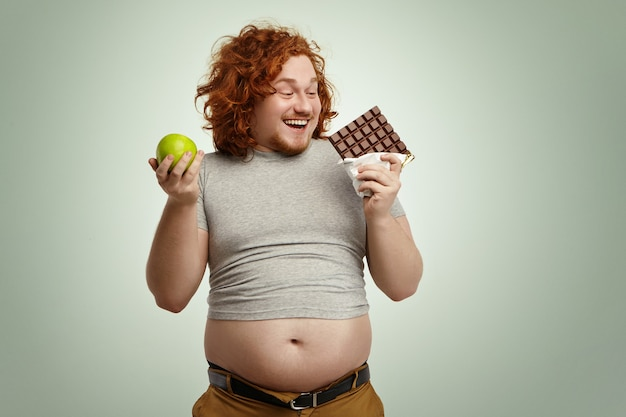 Portrait of happy fat young male, choosing bar of chocolate over fresh green apple