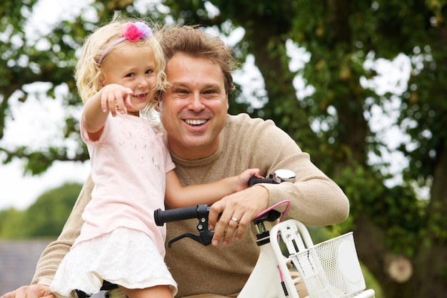 Portrait of happy father and daughter with bicycle in park