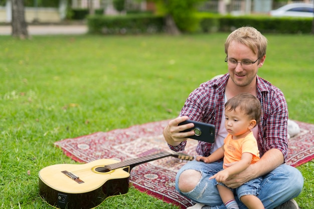 Portrait of happy father and multi-ethnic baby son bonding together outdoors