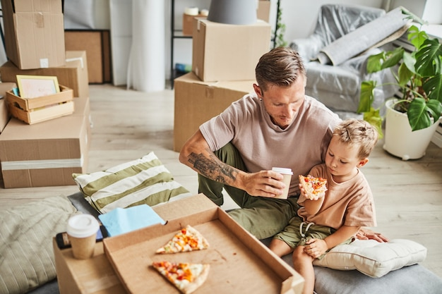Portrait of happy father and son eating pizza from cardboard box while celebrating moving in to new ...