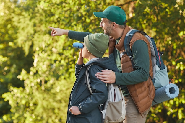 Portrait of happy father and son hiking together and pointing away while walking in forest with backpack, copy space