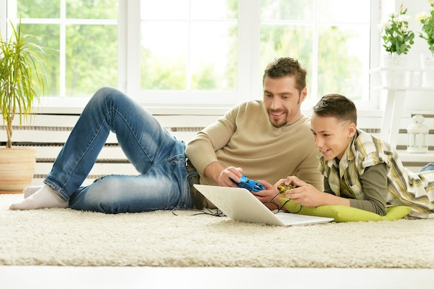 Portrait of happy father and son playing computer game at home