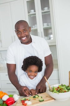 Portrait of happy father and son preparing vegetables
