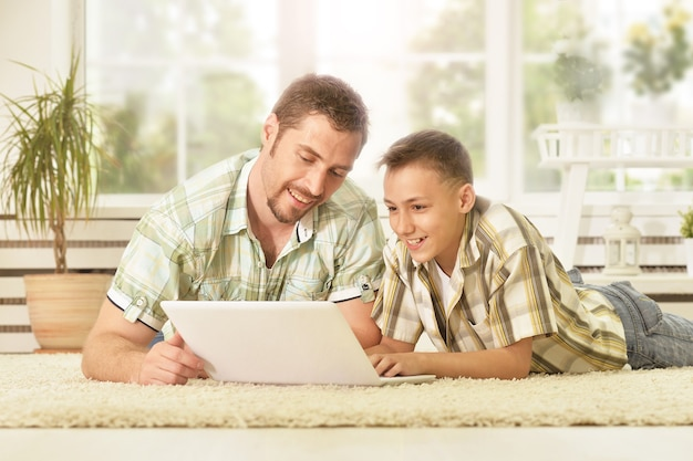 Portrait of happy father and son with laptop at home