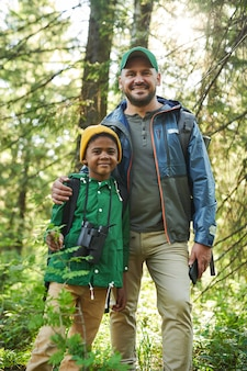 Portrait of happy father standing together with his son in the forest during their hiking