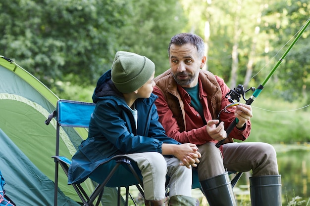 Portrait of happy father talking to little son while enjoying fishing trip together and camping in nature