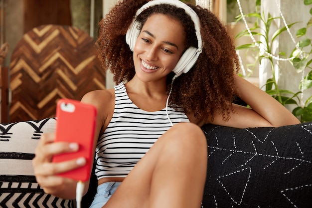 Portrait of happy female blogger publishes new photos on website, makes selfie on modern smart phone, listens favourite music in headphones, spends free time in cozy atmosphere, uses free wifi