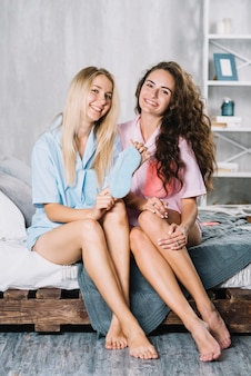 Portrait of happy female friends sitting on bed