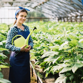 Portrait of a happy female gardener holding watering can in greenhouse