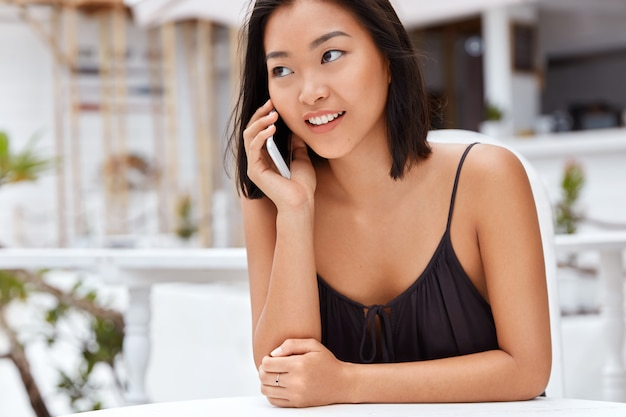 Portrait of happy female model has fun during leisure time in cafeteria, glad to speak with friend via mobile phone, enjoys sunny day. beautiful asian woman with pleased expression talks on mobile