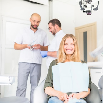 Portrait of happy female patient sitting in front of two male dentist