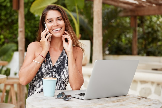 Portrait of happy female read latest news on internet website, shares information with close friend, use modern electronic gadgets for being always in touch, recreate in sidewalk coffee shop