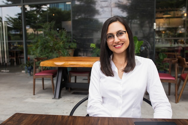 Portrait of happy female student in glasses sitting in cafe