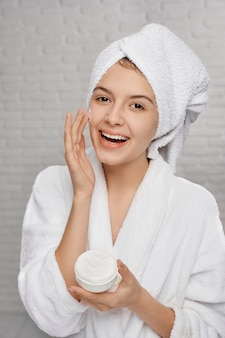 Portrait of happy female in towel applying cream face