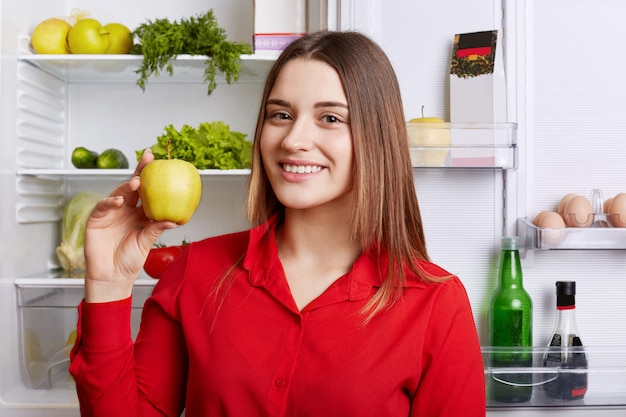 Portrait of happy female vegeterian holds fresh apple, stands near fridge with happy expression, keeps to diet, has fridge full of vegetables