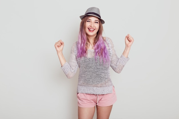 Portrait of happy female wearing hat, shirt and short, clenching fist with satisfied facial expression, celebrating triumph, looks at camera with toothy smile, isolated over grey background.