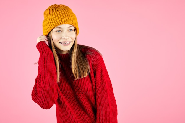 Portrait of happy female with broad smile. girl wears brackets on teeth and sweater with knitted hat, poses against pink wall.