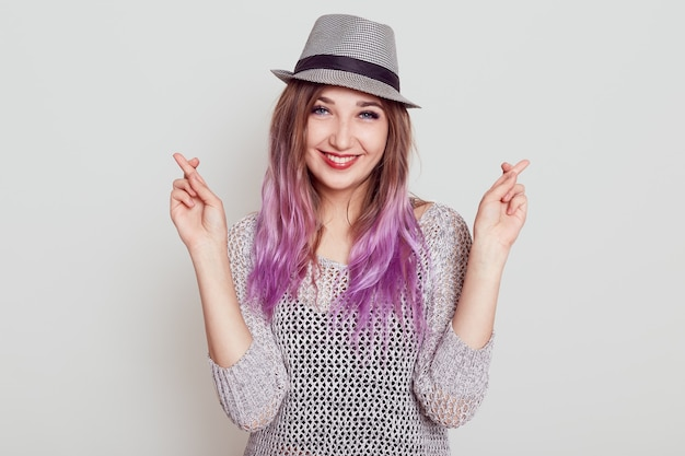 Portrait of happy female with pleasant appearance, crossing fingers, hopes for better, looking smiling at camera, wishes dream comes true, isolated over grey background.